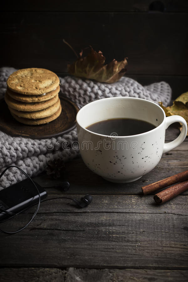 Cup of coffee/tea, cookies, fallen leaves, earphones, and scarf on wooden table. stock photo