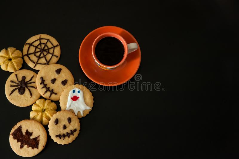 A Cup of coffee, terribly tasty cookies with terrible emoticons, cobwebs, spiders, bats, pumpkins on a black background. stock photos
