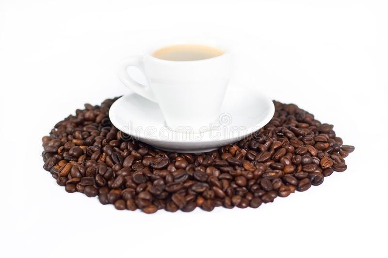 A cup of coffee on top of coffee beans royalty free stock images
