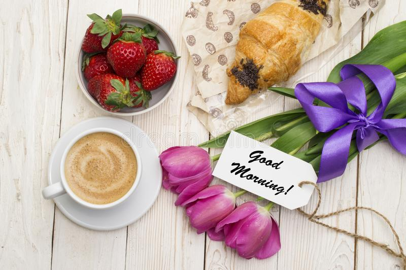 Cup of coffee, tulips, croissant, strawberries and Good morning massage on wooden background royalty free stock images