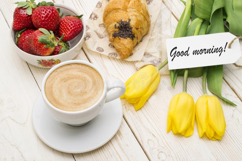 Cup of coffee, tulips, croissant, strawberries and Good morning massage on wooden background.  royalty free stock photography