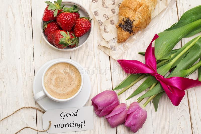 Cup of coffee, tulips, croissant, strawberries and Good morning massage on wooden background.  royalty free stock images