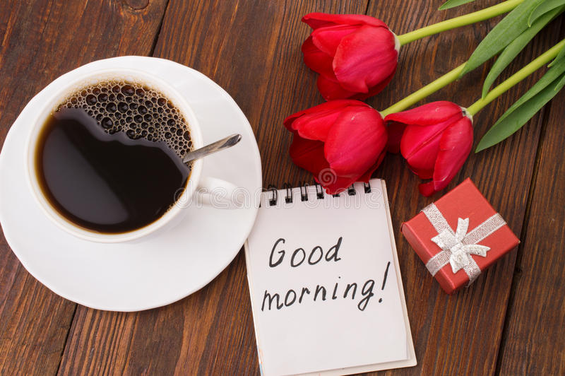 Cup of coffee, tulips and Good morning massage. On wooden background royalty free stock photos