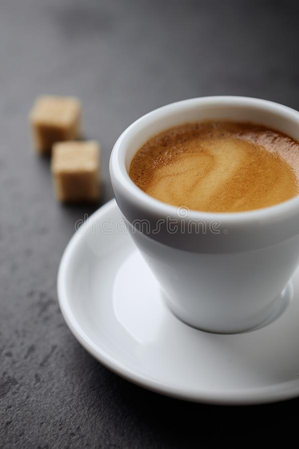 Cup of coffee and two brown sugar cubes on black stone background. royalty free stock photography