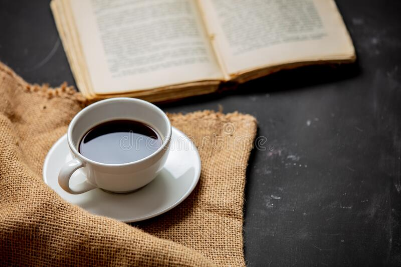 Cup of coffee and vintage book on a table stock photo