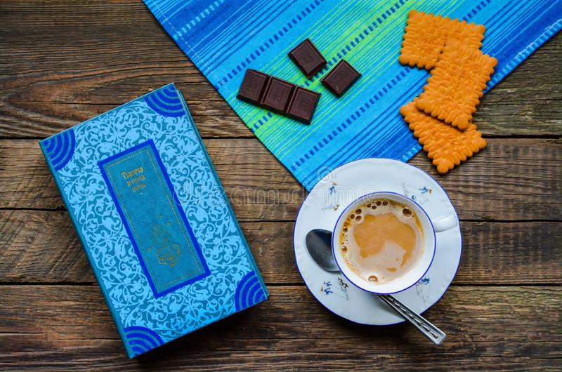 Cup of coffee, book and sweets. Always warm & tasty royalty free stock photo