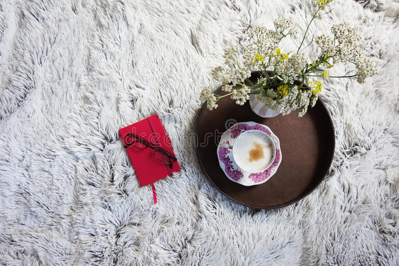 A cup of coffee warming in bed stock images