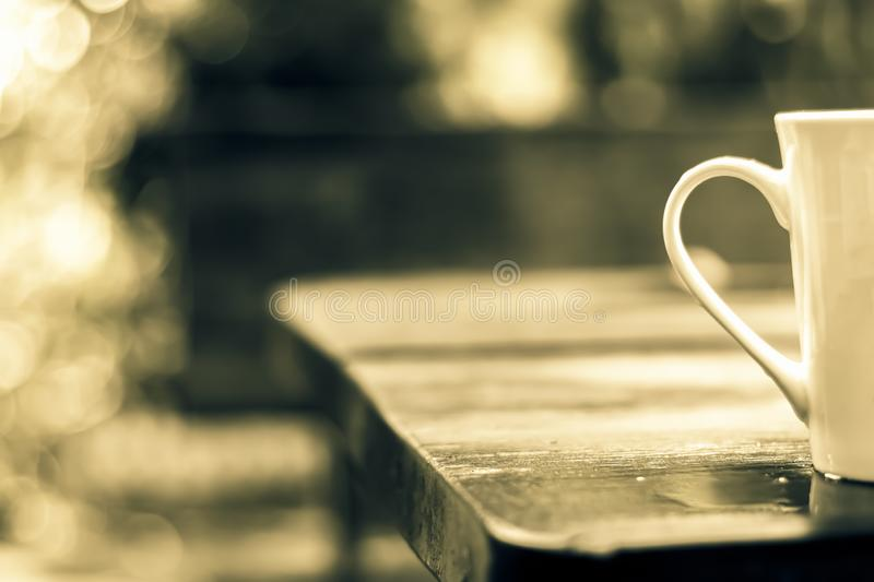 A cup of coffee was placed alone on a wooden table, wet rain. T royalty free stock photos