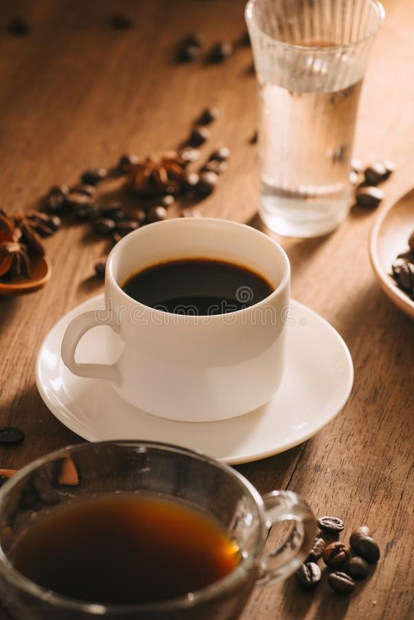 A cup of coffee with water, coffee beans and tea on wooden background royalty free stock photos