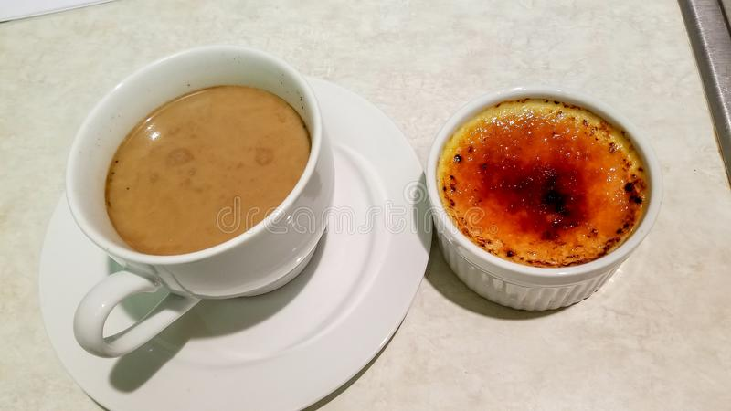 Cup of coffee in white ceramic cup next to creme brulee in white ceramic ramekin royalty free stock photo