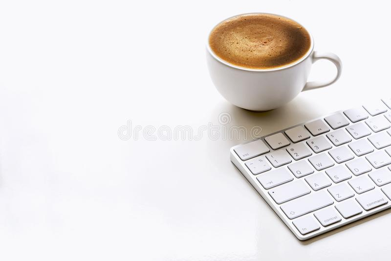 Cup of coffee and white keyboard on white table stock photo