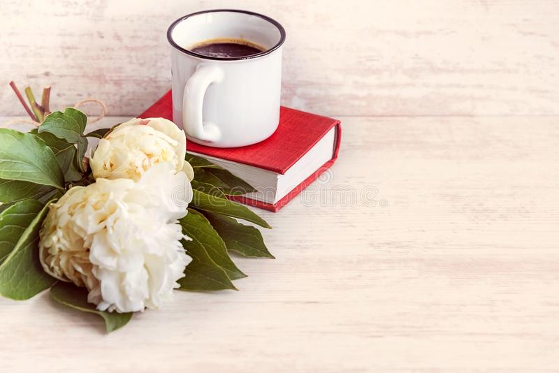 A cup of coffee, white peonies and a red book over a white wooden background. stock images