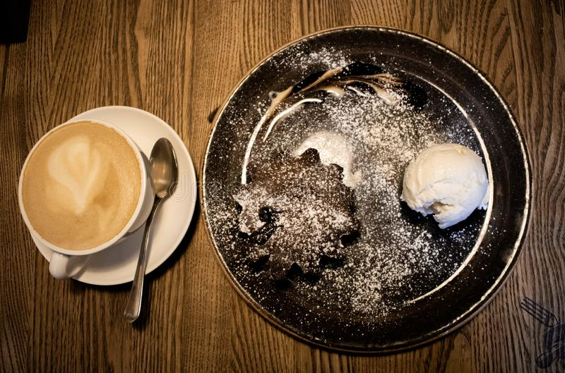 Cup of coffee on a white saucer with chocolate muffin and ice cream royalty free stock photo