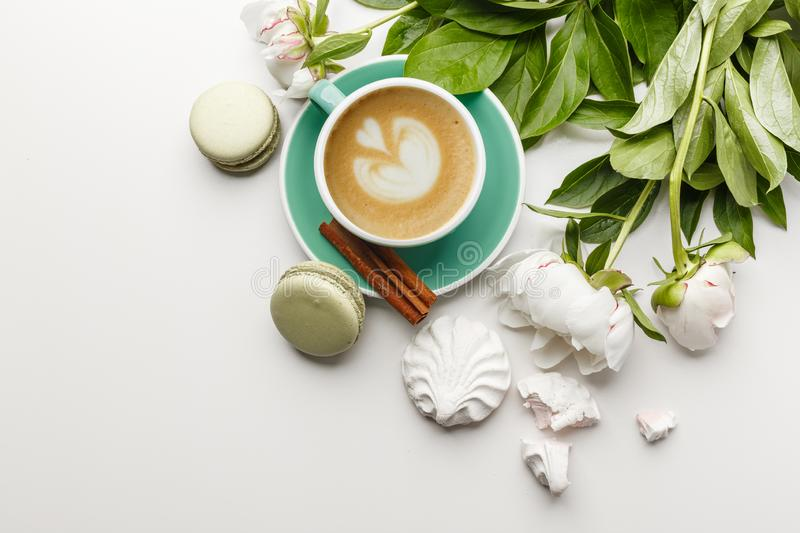 A cup of coffee on a white table with peonies, sweets and fruits royalty free stock photography