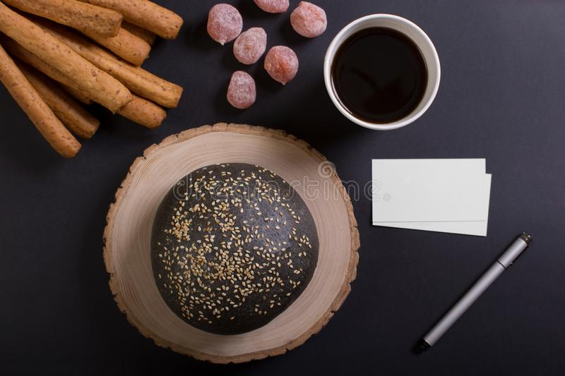 Business breakfast with cup of coffee. Cup of coffee whith lump of sugar and some candy. Black loaf and breadstick. Top view with copyspace for your text stock image