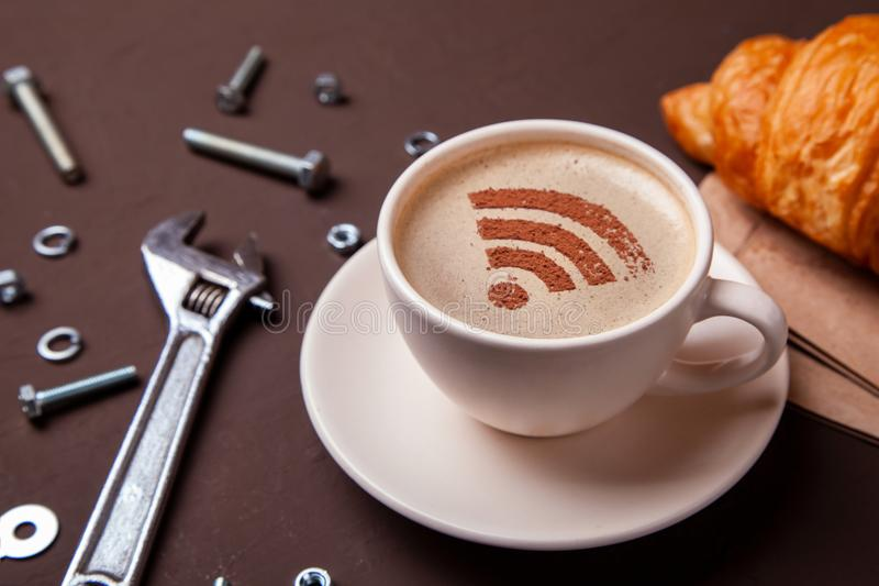 Cup of coffee with WiFi sign on the foam. Free access point to the Internet WiFi. Repair service concept. Technical support wrench stock image