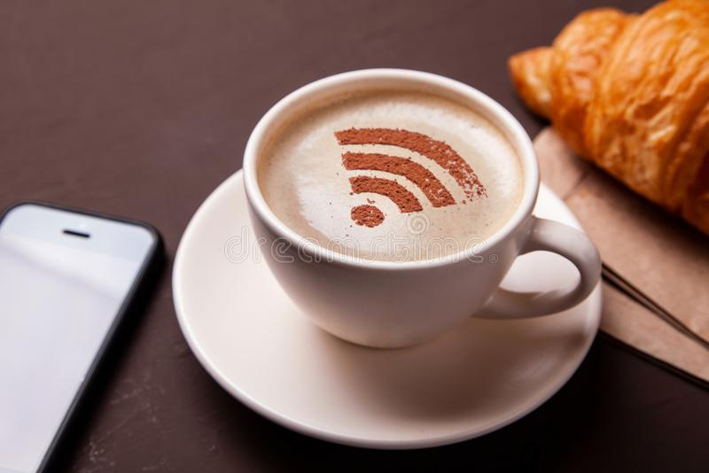 Cup of coffee with WiFi sign on foam. Free access point to the Internet WiFi. I like coffee break with croissant royalty free stock photos