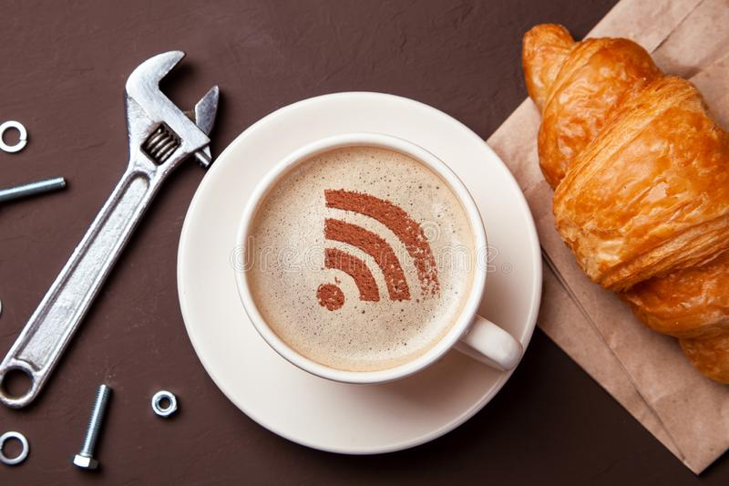 Cup of coffee with WiFi sign on the foam. Free access point to the Internet WiFi. I like coffee break with croissant stock image