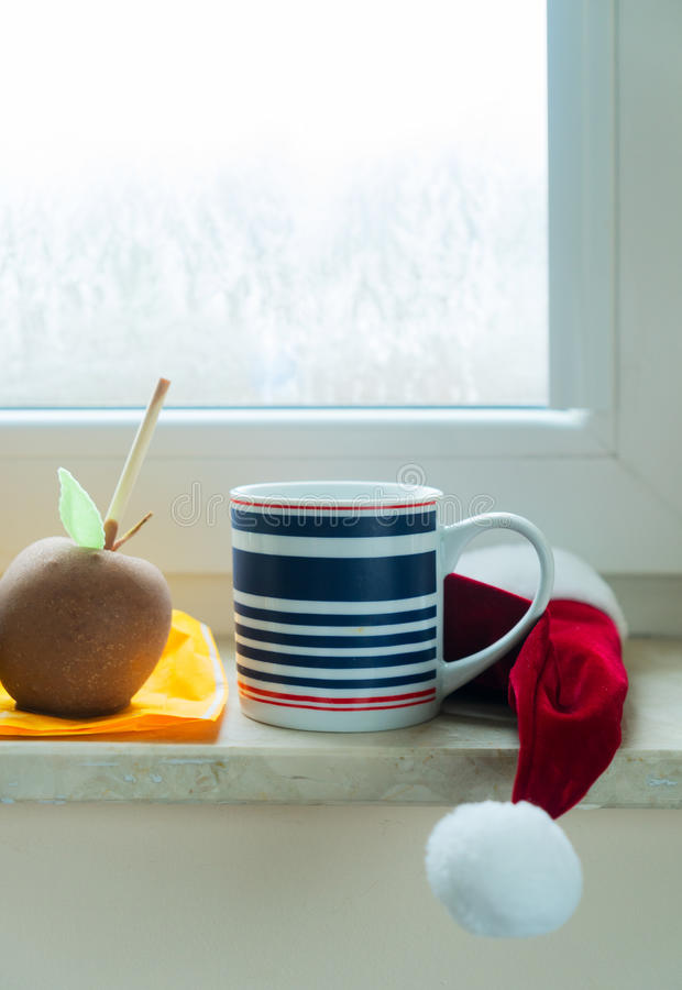 Cup of coffee on window sill. Mug of coffee on christmas window sill with apple glazed in chocolate stock photo