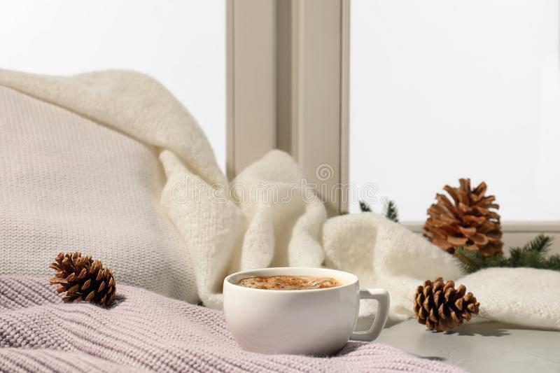 Cup of coffee on windowsill indoors. Winter drink. Cup of coffee on windowsill indoors, space for text. Winter drink royalty free stock image