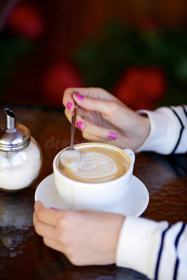 Cup of coffee, woman hands and sugar pot on table. Closeup royalty free stock photography
