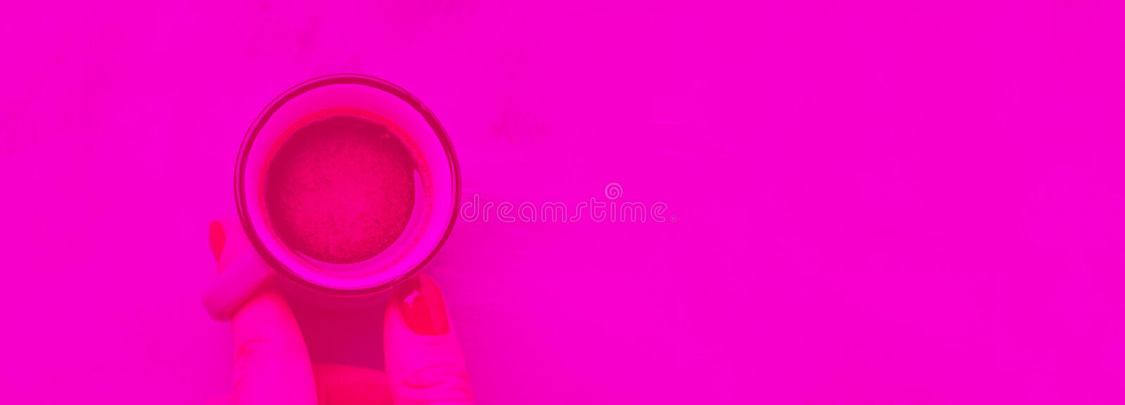 Cup of coffee in woman`s hand. Vibrant pink toned stock photography