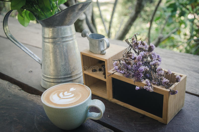 A cup of coffee with latte art on the wood table in vintage style stock photography