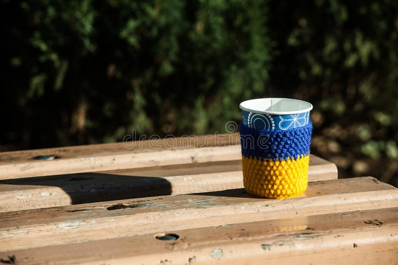 Cup coffee wooden bench covered snow mornimg yellow blue heat knitting stock photography