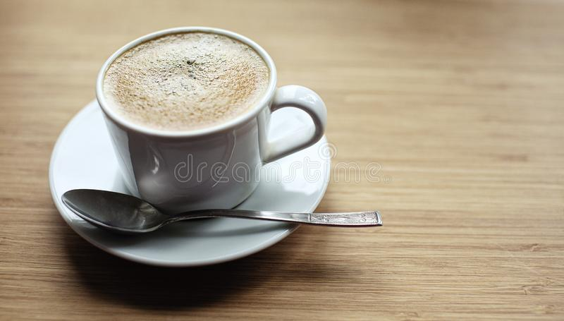 Cup of coffee on wooden desk. Breakfast in the morning royalty free stock images