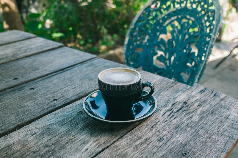 Cup of coffee on wooden table stock photography