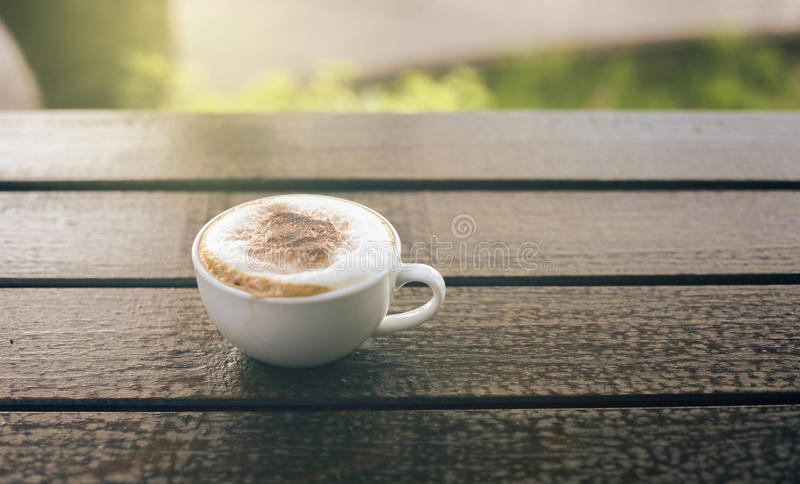 Cup of coffee on wooden table with blurred background,warm tone picture,filtered image,selective focus,light effect added stock photography