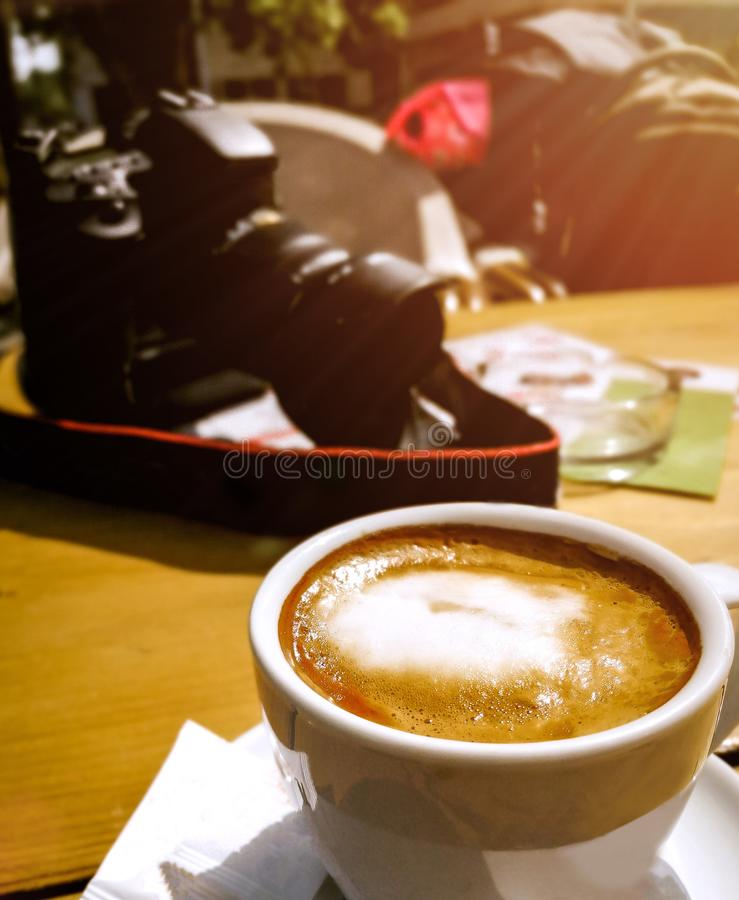 Cup of coffee on the wooden table with DSLR camera in the background. And sunlight stock image