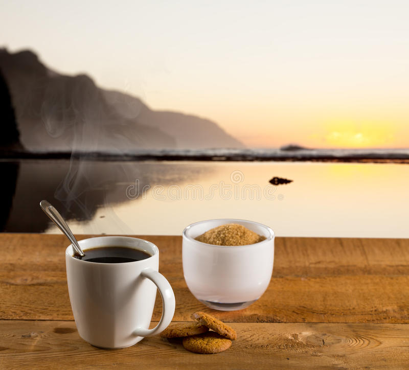 Cup of coffee on wooden table by ocean