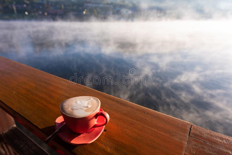 A cup of coffee on wooden table with steam over lake at Rak thai village royalty free stock image