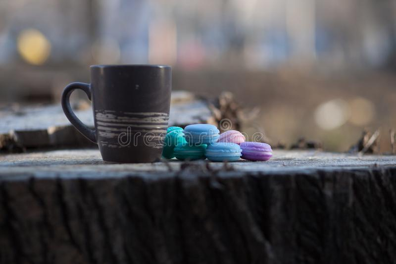 Cup of coffee on a wooden table in the sun. With sparkles and blur in the background. ecological breakfast. Macarons with blue, purple and chocolate color royalty free stock image