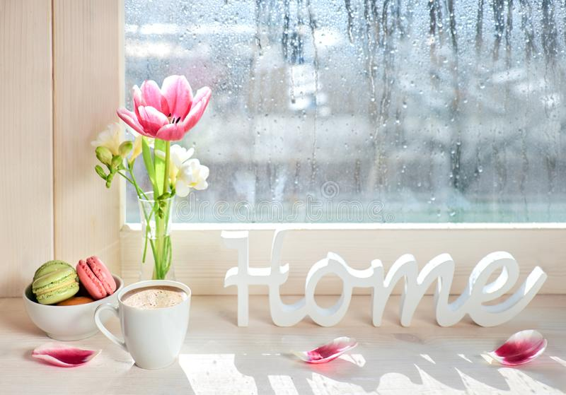 Cup of coffee, word. `Home`, pink tulips and white freesia on the window board on a rainy day in Spring stock photo