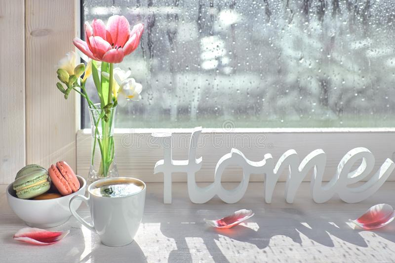 Coffee cup, word. Cup of coffee, word `Home`, pink tulips and white freesia on the window board royalty free stock image