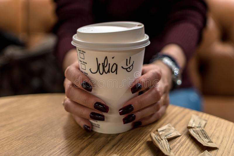 Cup of coffee with writen word JULIA in woman hand.  stock photos