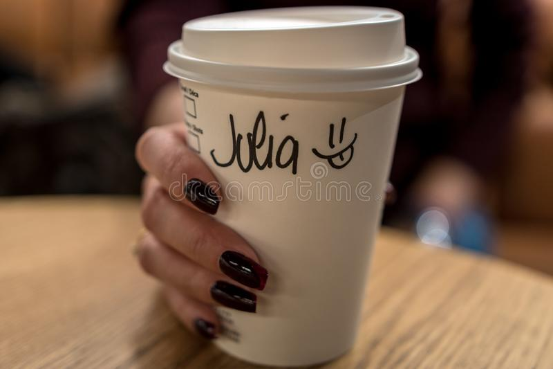 Cup of coffee with writen word JULIA in woman hand.  royalty free stock image