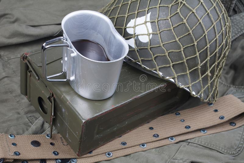 A cup of coffee with ww2 period us army military equipment on green uniform. Background concept stock photo