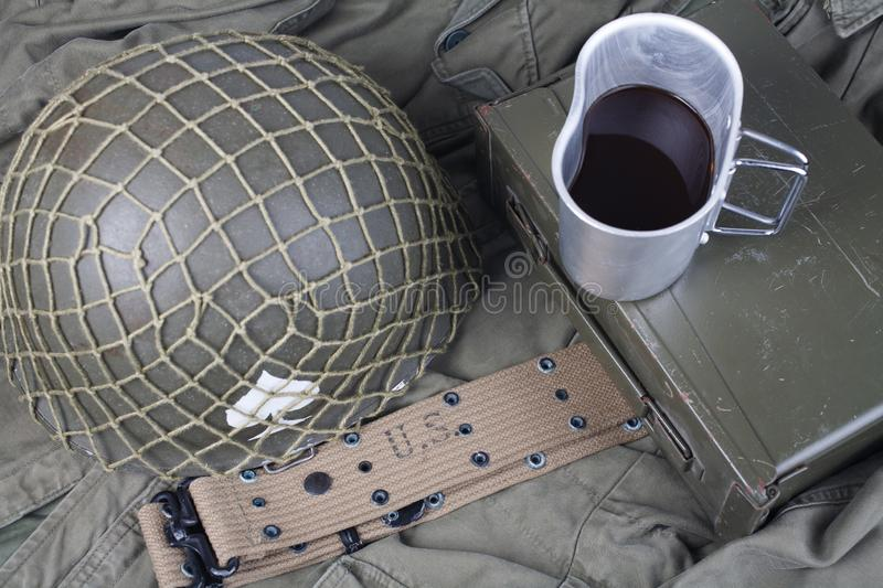 A cup of coffee with ww2 period us army military equipment on green uniform. Background concept stock photography