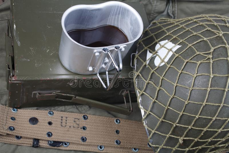 A cup of coffee with ww2 period us army military equipment on green uniform. Background concept royalty free stock photo