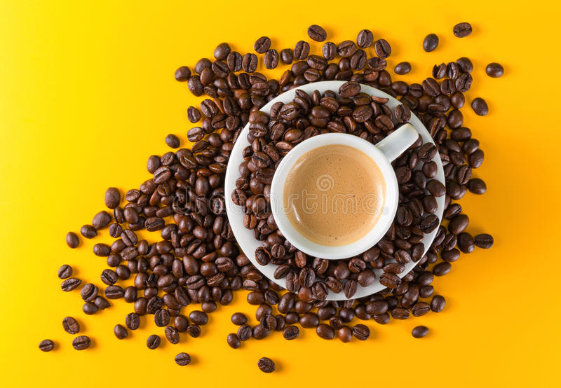 Cup coffee yellow background. Espresso Cup coffee beans on yellow background stock photo