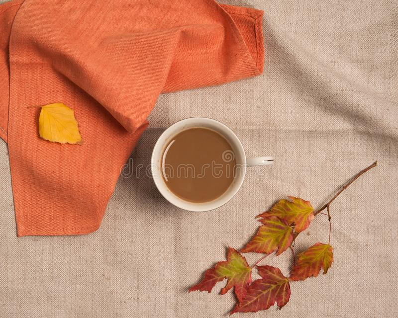 A cup of coffee, yellow birch leaves, red maple leaves on a beige linen napkin. stock photos
