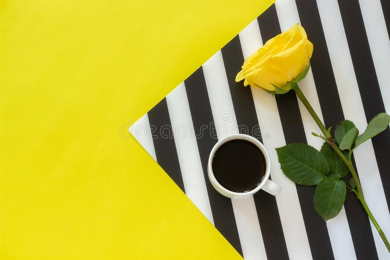 Cup of coffee and yellow rose on stylish black and white napkin on yellow background. Minimal style. Concept good morning or day. Flat lay Top view Copy space stock image