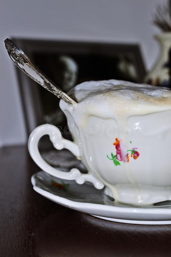 Cup of coffeee overflowing. Close-up of vintage cup overfloving with cappuccino stock photos
