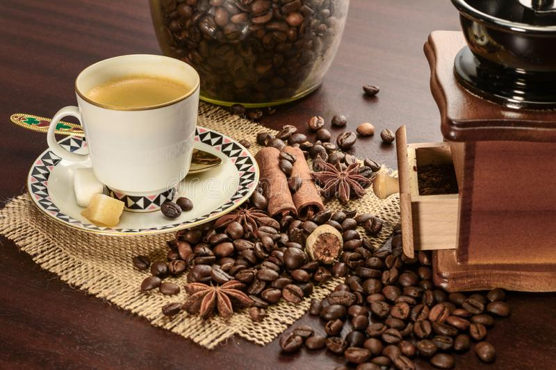Cup of coffeee with saucer on a jute napkin. Vintage still life on wooden table with sugar, anise, cinnamon, grinder and coffee. Cup of coffeee with saucer on a royalty free stock images