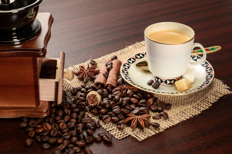 Cup of coffeee with saucer on a jute napkin. Vintage still life on wooden table with sugar, anise, cinnamon, grinder and dropped. Cup of coffeee with saucer on a royalty free stock image