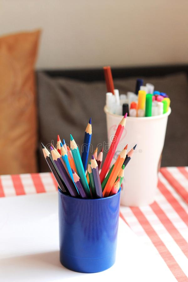 Cup with colorful pencils on table. Paper and a set of markers. Cup with colorful pencils on table. White paper and a set of markers stock photo