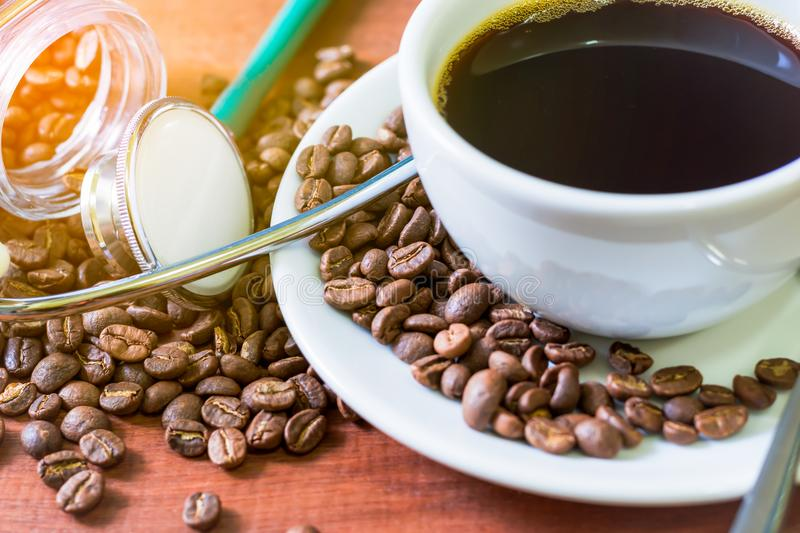 Cup of dark coffee with coffee beans and stethoscope on wooden background. Health concept of who like drink a coffee royalty free stock image